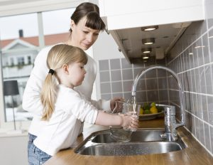 Girl filling up glass with water - Soft water benefits