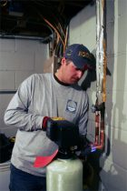 Peterson Salt employee repairing residential water softener